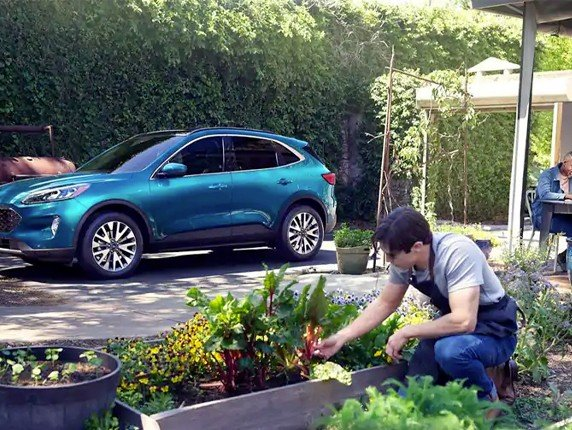 A man and woman working in their yard with a 2020 Ford Escape parked in the background