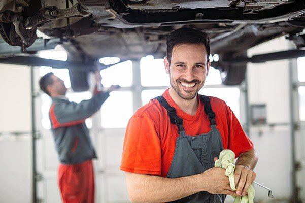 auto technician completing an oil change on a car