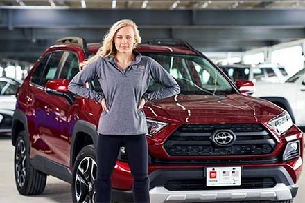 Jessica Long standing in front of a new Toyota SUV.