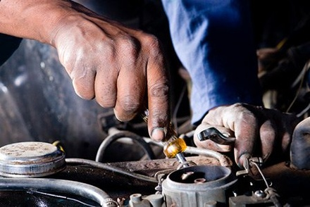 Mechanic at Westbury Toyota on Long Island performing engine tune-up.