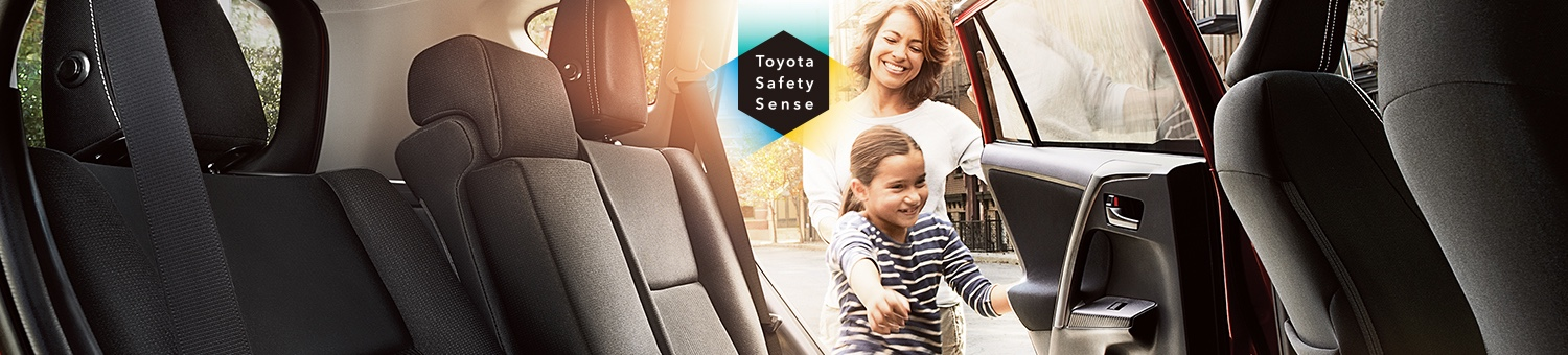 Little girl getting into the back seat of a new toyota rav4 suv