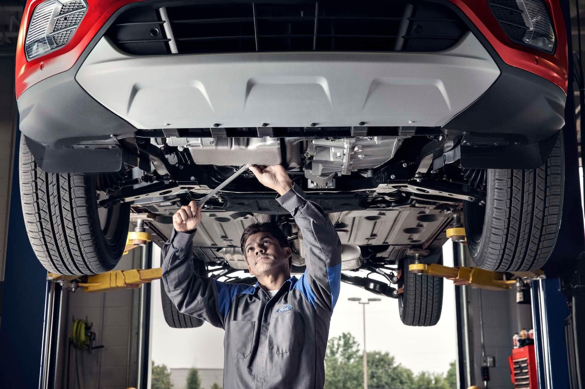 Quick Lane - Service Technician Inspecting Vehicle on Lift