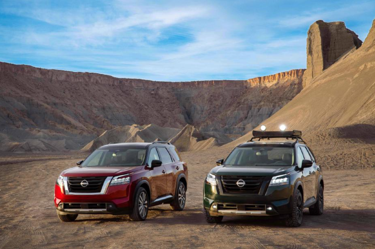 Two 2022 Nissan Pathfinder vehicles parked in a desert next to each other.