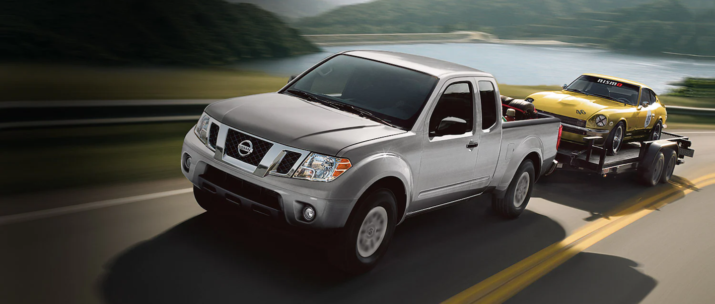 The 2021 Nissan Frontier towing a classic car.