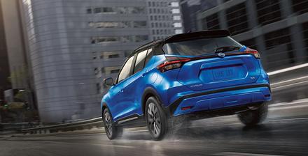 A Electric Blue Metallic 2021 Nissan Kicks driving through a city like Orlando.