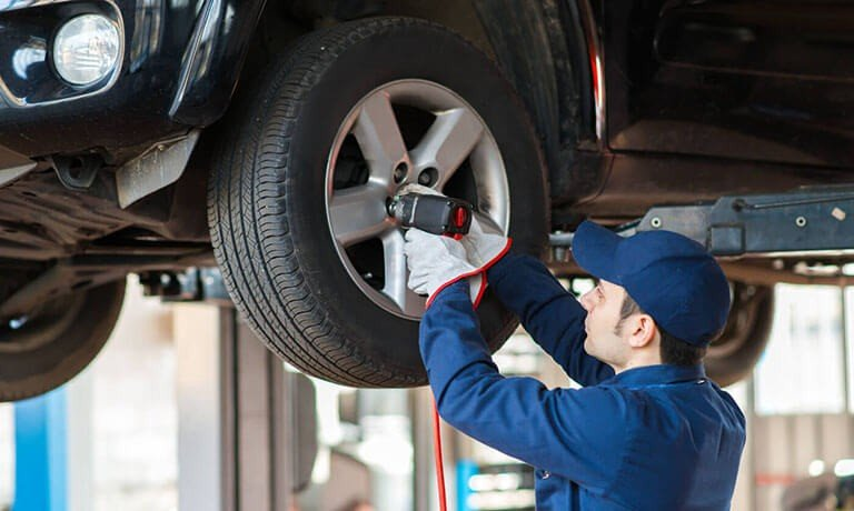 Mechanic Removing a tire on a raised vehicle