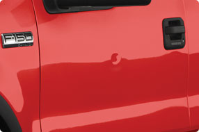 drivers side door dent in a red ford f150 truck