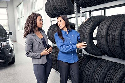 service advisor and customer browsing tires