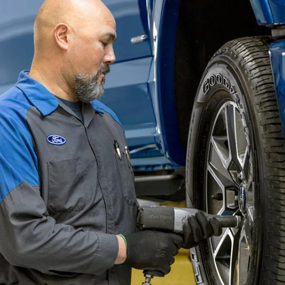 technician tightening lug nut on tire