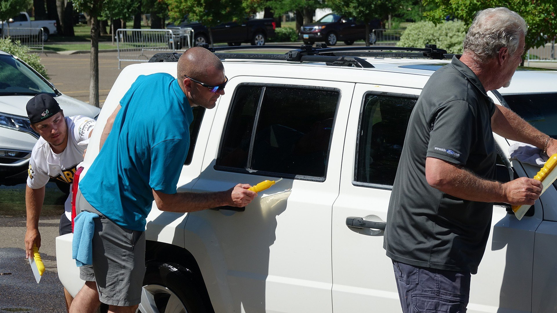 Eide Ford and Chrysler employees washing cars in Bismarck