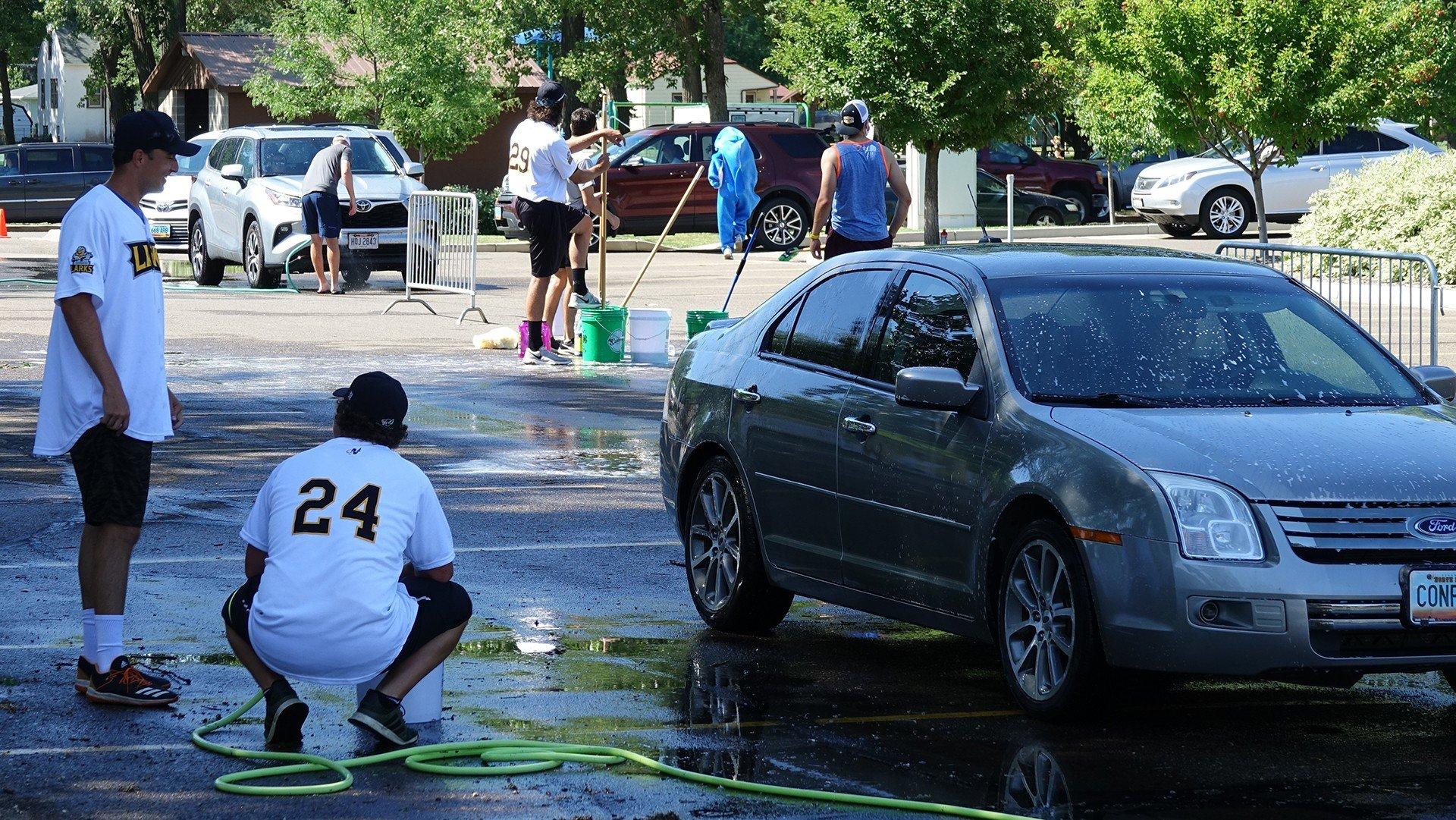 Larks players take a break while washing cars in Bismarck.