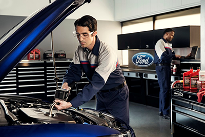Ford certified mechanic adding oil to a blue ford focus