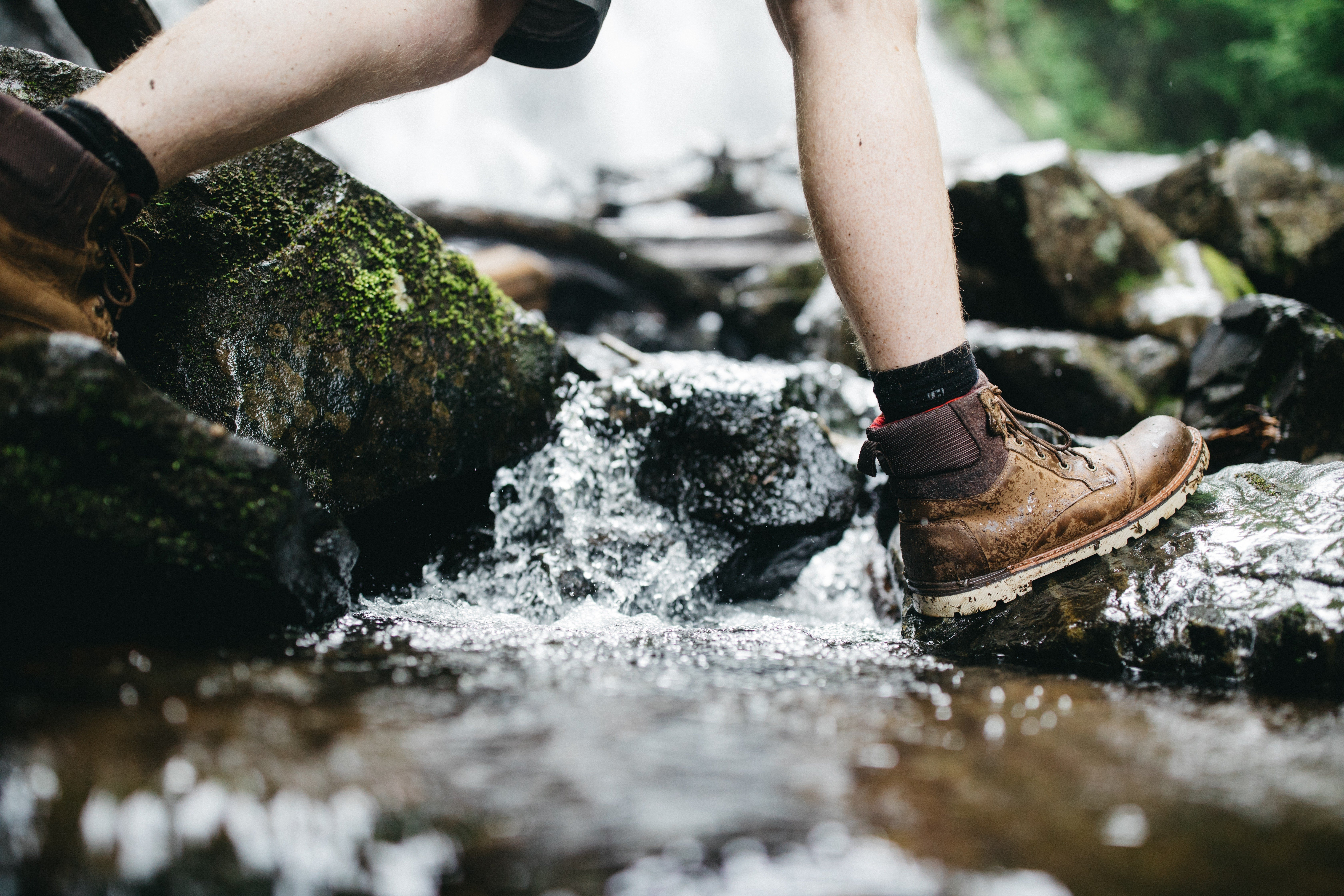 The legs of a well prepared hiker in leather hiking boots stepping on stones as they cross a mountain stream.