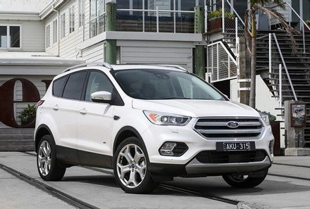 A white Ford Escape parked in front of a suburban home.