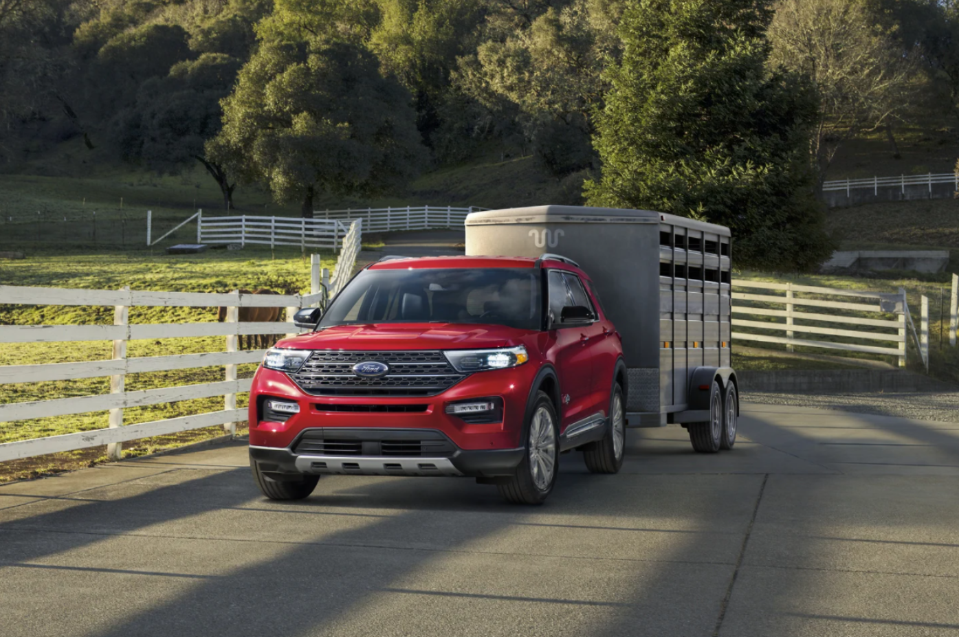 A red 2021 Ford Explorer pulling a horse trailer down the road at a local farm.