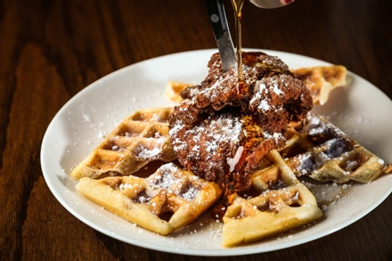 Fluffy waffles covered by crispy fried chicken and sweet maple syrup.