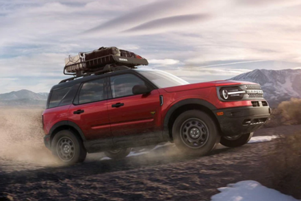 A new red 2021 Ford Bronco Sport driving along a sand dune while loaded with equipment for an extended adventure.
