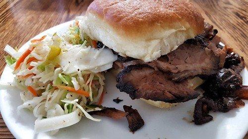 A juicy smoked brisket sandwich alongside fresh coleslaw at a local Dallas, TX BBQ spot.