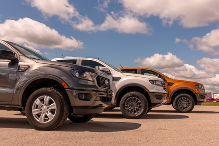 A lineup showing three of the new Ford Rangers painted in gray, white, and orange.