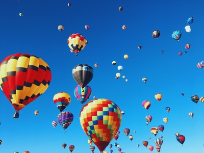A festival full of hot air balloons rising into a clear fall sky.
