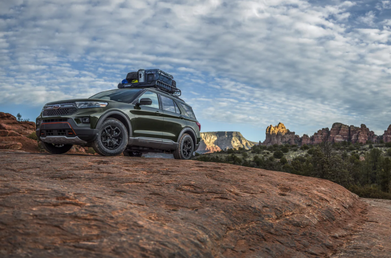 A green 2021 Ford Explorer packed for an adventure parked on top of a rocky crag.