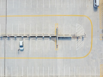 An aerial shot of a large parking lot with only two small white vehicles left in view.