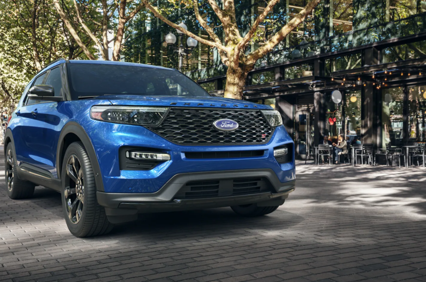 A blue 2021 Ford Explorer looking both rugged and stylish in front of a downtown bistro.
