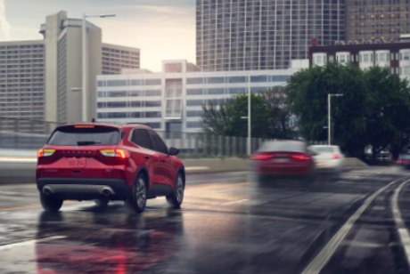 A red 2021 Ford Escape driving down a rainy freeway into the city.