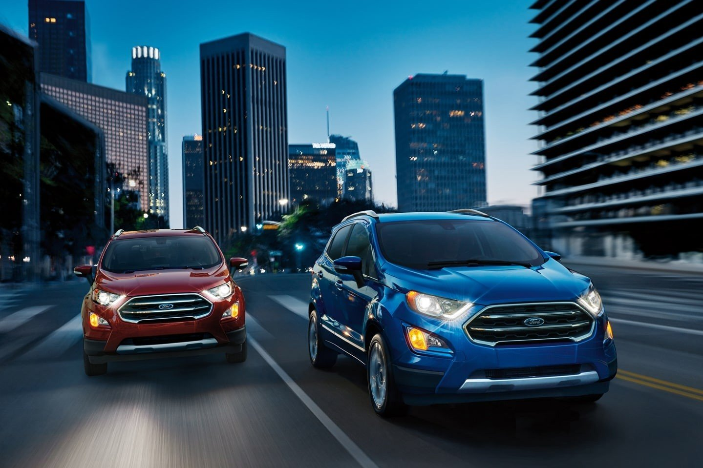 A red and blue 2021 Ford EcoSport driving down the freeway through a major city.