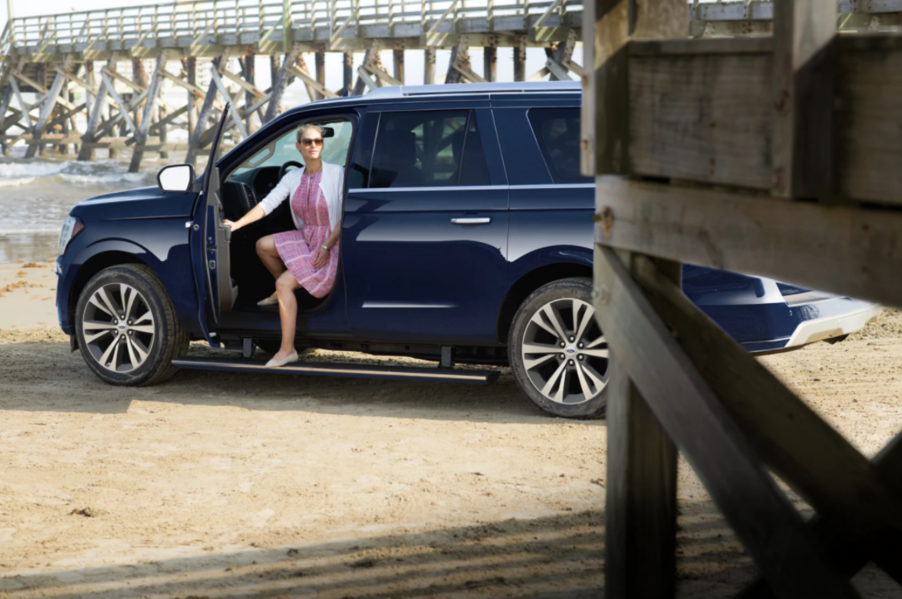 A women in a pink dress exiting a blue 2021 Ford Expedition parked on the beach.