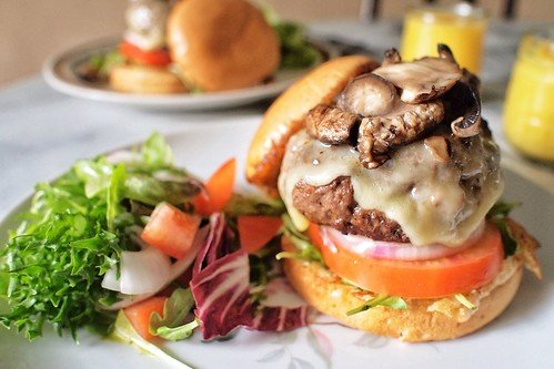 A juicy and delicious, handmade burger covered in cheese and mushrooms on fresh tomato and a locally made bun.