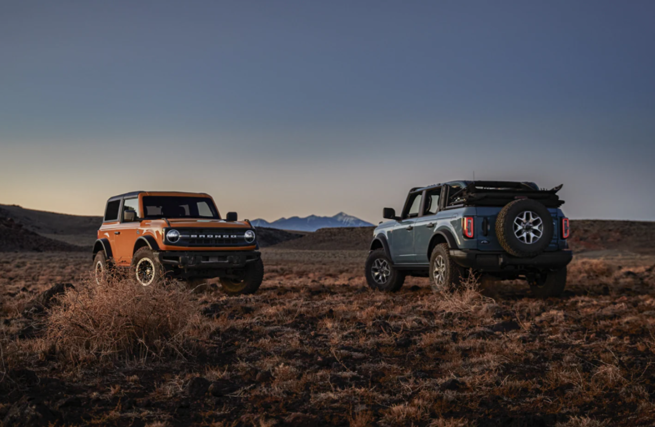 An orange hardtop 2021 Ford Bronco and a blue soft-top Bronco parked on an expansive prairie with mountains in the distant background.