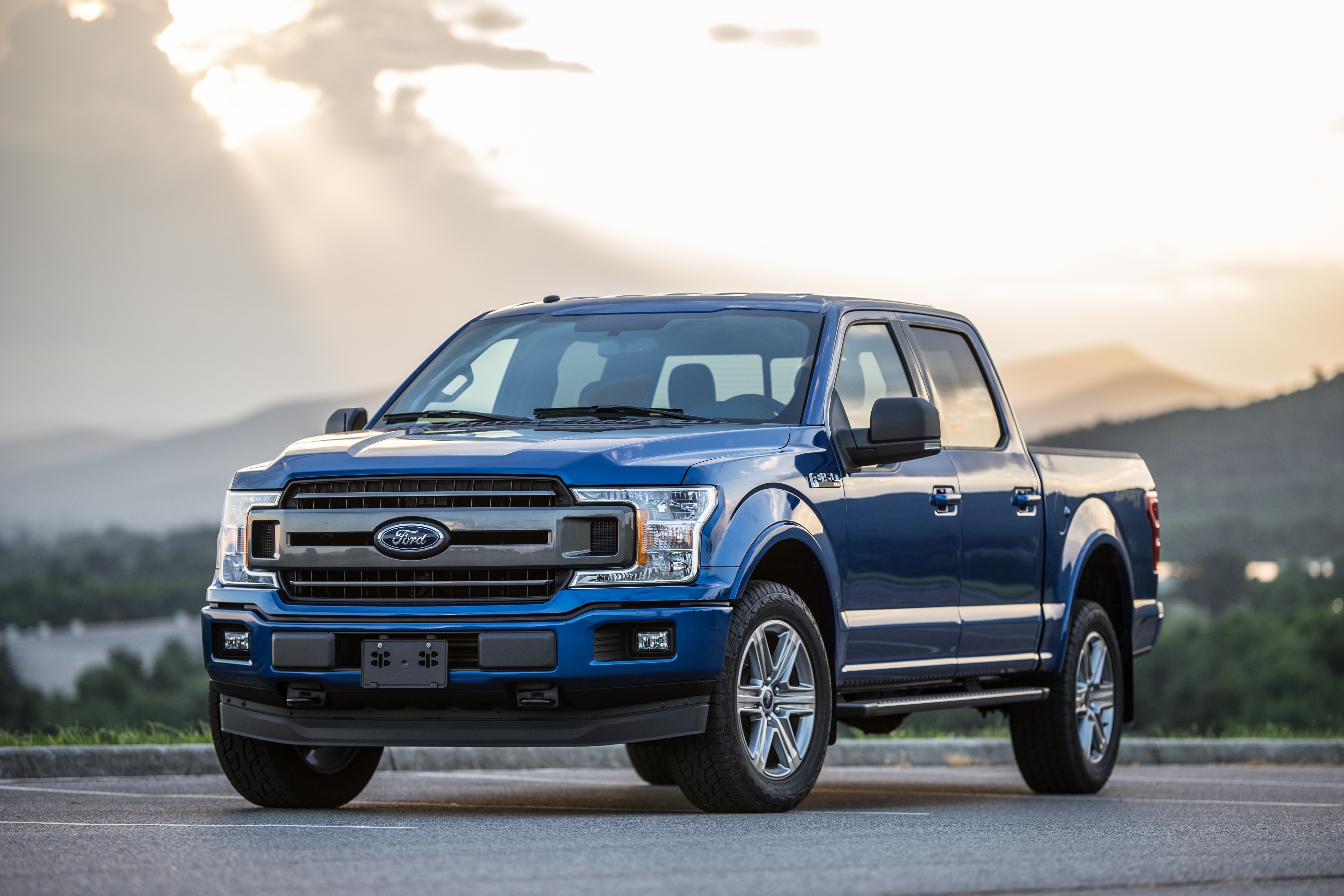 A blue Ford F-150 parked in front of a lake with the evening sun streaming through the dissipating clouds.
