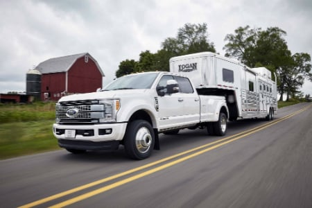 2017 ford f-series super duty pulling a trailer at the farm