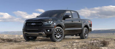 Absolute Black color 2019 Ford Ranger exterior front fascia and drivers side parked in wilderness