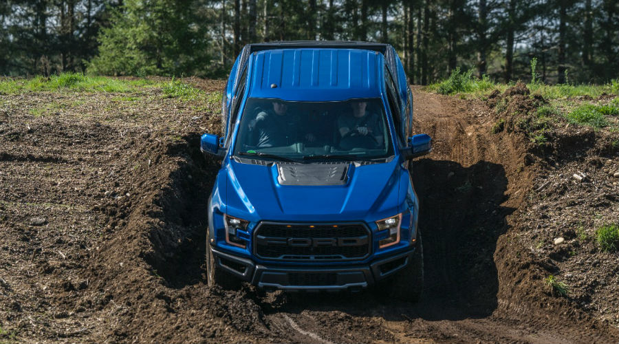 blue 2017 Ford F-150 Raptor driving down a dirt hill