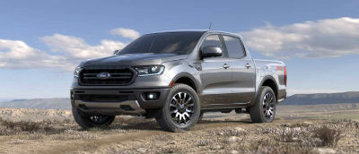 Ingot Silver color 2019 Ford Ranger exterior front fascia and drivers side parked in wilderness