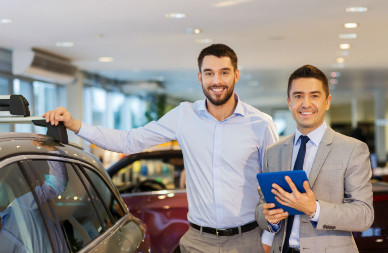 man and sales man standing next to car