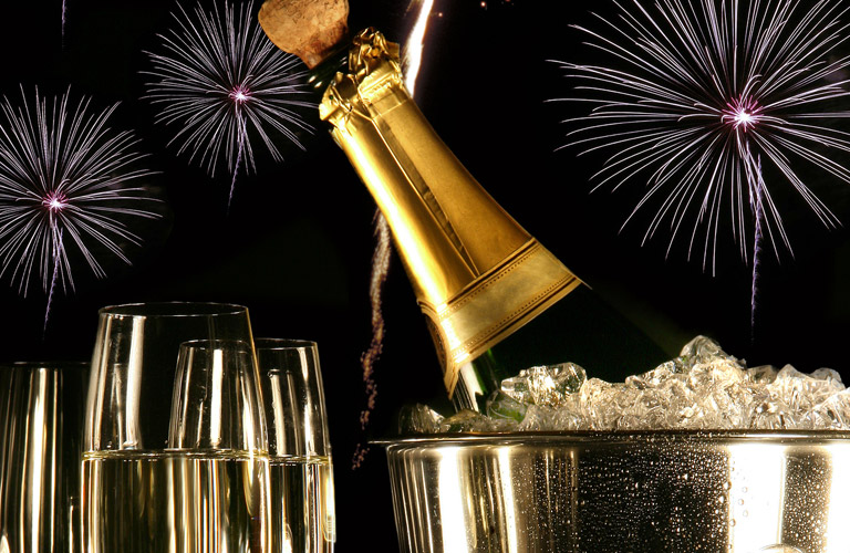 opening a bottle of champagne with multiple glasses and a bucket of ice, fireworks in the background