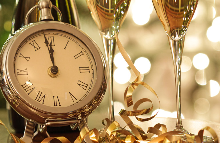 clock right before midnight next to 2 glasses of champagne with NYE decorations