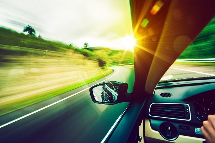 Image of a country highway out the window of the driver's side of a car.