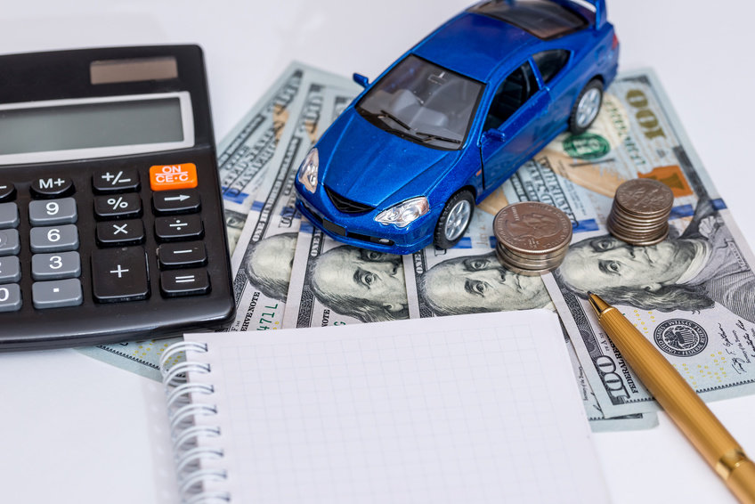 Image of a blue toy car, a notepad, and a calculator on top of $100 bills.