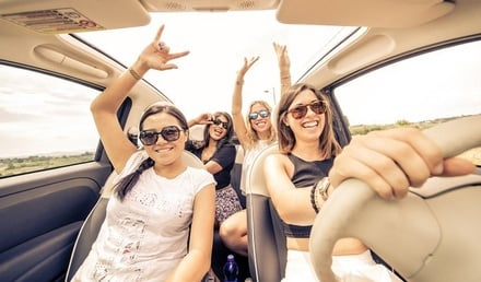 Image of a group of young women driving in a car with sunglasses on and their hands up.