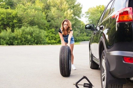 Image of a woman rolling a spare tire toward her car.