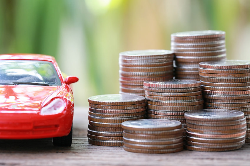 Image of a red toy car next to a stack of coins.