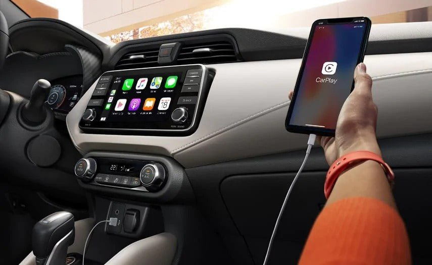 A hand holding an iPhone that reads CarPlay from the passenger seat of a Nissan